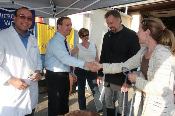 Mayor Aronsohn of Ridgewood greeting a pet owner before microchipping at the clinic. Dr. Mosaad, Jeffrey Ball and Kim Luikert look on.