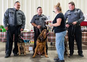 Valeria Burton of the Conroe Kennel Club gives Montgomery County Constable Precinct 4 Deputy Jesse Bullinger a check for $1,861 to purchase protective vests for Oliver the bloodhound and another dog. Pictured are Eric Prado with Dino, Bullinger with Oliver, center, and Bryan Skero with Hashish. Photo credit: Michael Minasi